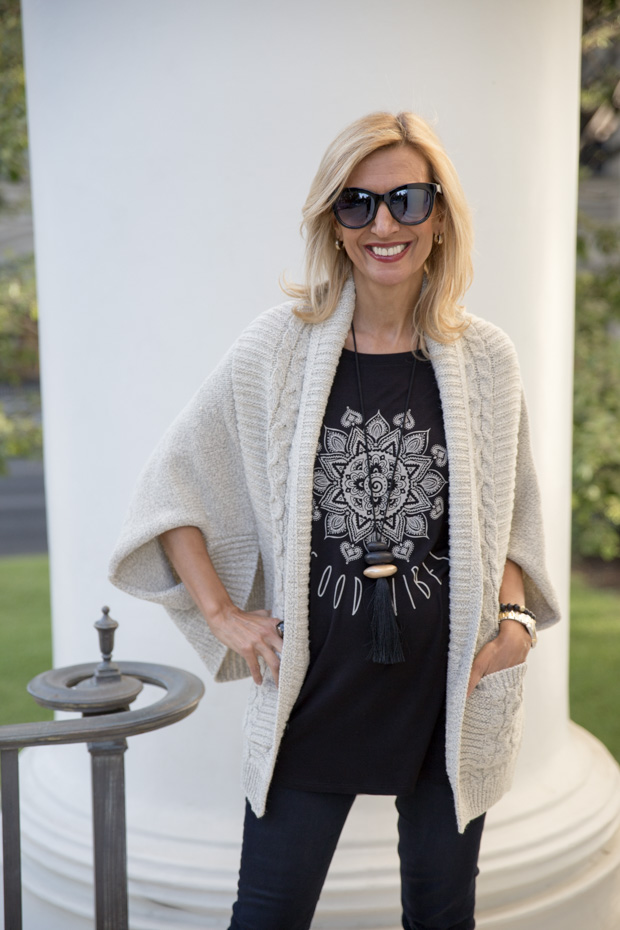 black soft rayon t shirt with good vibes worn with beige knit cable shrug